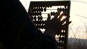 Kvinna i svarta flyttningpärlor på kulrammet på naturen lager videofilmer