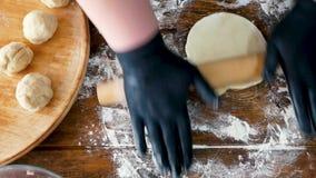 Kvinna i svarta handskar som rullar deg med kavlen för framställning av pizza eller av pajen stock video