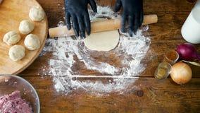 Kvinna i svarta handskar som rullar deg med kavlen för framställning av pizza eller av pajen lager videofilmer
