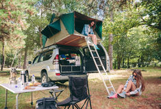 Kvinna i tält över 4x4 och annan som sätter att fotvandra Royaltyfri Fotografi