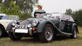 Kvinna i tappningklänning och den klassiska Morgan sportbilen Arkivbild