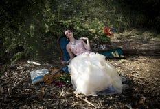 Kvinna i tappningsömnadklänning som vilar på rokokostol under en förtrollad skog arkivfoton