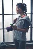 Kvinna i telefon för genomkörarekugghjulinnehav och yoga som är matt i vindidrottshall Arkivfoto