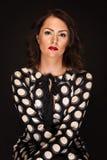 Kvinna i tillfällig stil på svart bakgrund med glamourljus Arkivfoton