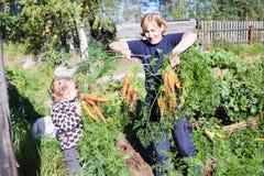 Kvinna i trädgård med barnet Royaltyfria Bilder