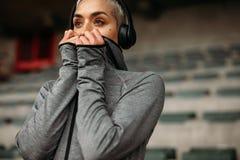 Kvinna i tröjan som står i en stadion som lyssnar till musik fotografering för bildbyråer