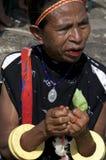 Kvinna i traditionell kläder genom att använda beatlenut Arkivbild