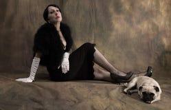 Kvinna i trettiotalstil med mopshunden Fotografering för Bildbyråer