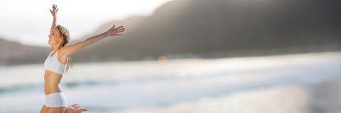 Kvinna i underkläder som firar mot den oskarpa kustlinjen Arkivbilder