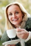 Kvinna i utomhus- Cafe med den varma drinken Arkivfoto