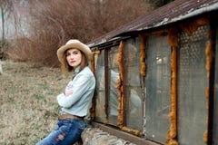 Kvinna i västra kläder i cowboyhatt, jeans och cowboykängor royaltyfria foton