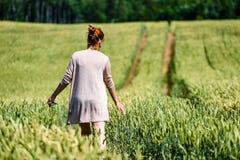 Kvinna i vetefält som tycker om tystnad Fotografering för Bildbyråer