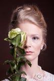Kvinna i victorianklänningen som täcker hennes öga med en ros Arkivfoton