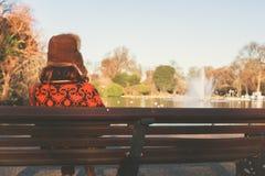 Kvinna i vinterhattsammanträde på bänk Royaltyfri Foto