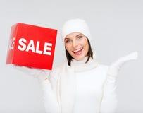 Kvinna i vinterkläder med det röda försäljningstecknet Arkivfoto