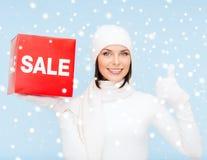 Kvinna i vinterkläder med det röda försäljningstecknet Arkivfoton