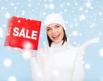 Kvinna i vinterkläder med det röda försäljningstecknet Arkivbilder