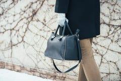 Kvinna i vinterlag som går på gatan med handväskor arkivfoton