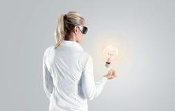Kvinna i virtuell verklighetexponeringsglas som ser till hologrammet som isoleras Royaltyfria Bilder
