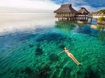 Kvinna i vit bikinisimning i koralllagun, Moorea, Tahiti royaltyfria bilder