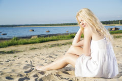 Kvinna i vit klänningflathet på stranden Fotografering för Bildbyråer