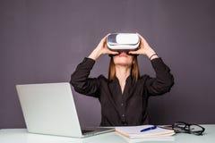 Kvinna i VR-exponeringsglas Säker ung kvinna i virtuell verklighethörlurar med mikrofon som pekar i luften, medan sitta på hennes Arkivbilder