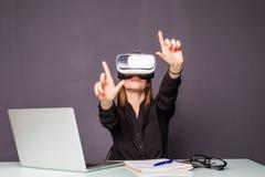Kvinna i VR-exponeringsglas Säker ung kvinna i virtuell verklighethörlurar med mikrofon som pekar i luften, medan sitta på hennes Royaltyfria Foton