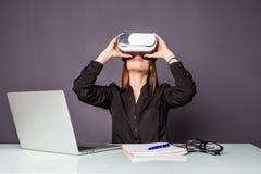 Kvinna i VR-exponeringsglas Säker ung kvinna i virtuell verklighethörlurar med mikrofon som pekar i luften, medan sitta på hennes Arkivfoto