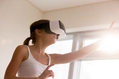 Kvinna i VR-exponeringsglas som trycker på objekt i världen 3d Arkivbilder