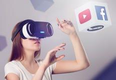 Kvinna i VR-hörlurar med mikrofon som ser upp och påverkar varandra med objekt Arkivbilder