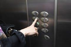 Kvinna inom en hiss som trycker på en knapp av asken fotografering för bildbyråer