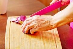 Kvinna klippt röd lök på skärbräda Arkivfoton