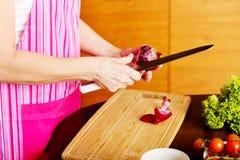 Kvinna klippt röd lök på skärbräda Royaltyfria Bilder
