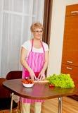 Kvinna klippt röd lök på skärbräda Fotografering för Bildbyråer