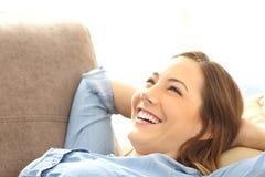 Kvinna kopplat av ligga på en soffa royaltyfria bilder