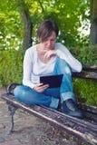 Kvinna läsande EBook på den digitala minnestavladatoren Arkivfoto
