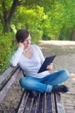 Kvinna läsande EBook på den digitala minnestavladatoren Royaltyfria Bilder