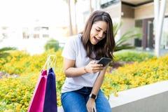 Kvinna läsande SMS på Smartphone vid shoppingpåsar utanför galleria fotografering för bildbyråer
