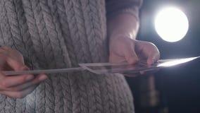 Kvinna med ögonblickliga trycköverföringsbilder i händer se polaroidfoto av vägturen i mörkt rum stock video