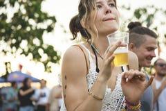 Kvinna med öl som tycker om musikfestival arkivbilder