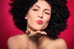 Kvinna med afro som blåser en kyss Arkivbild
