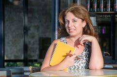 Kvinna med anteckningsboken och penna i stången Fotografering för Bildbyråer