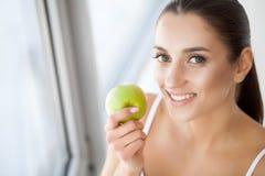 Kvinna med Apple Härlig flicka med det vita leendet, sunda tänder Royaltyfri Bild
