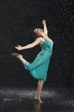 Kvinna med armar som tycker om ut regnet arkivfoto