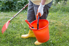Kvinna med att arbeta i trädgården utrustning i trädgård royaltyfri foto