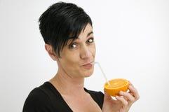 Kvinna med att dricka sugrör och apelsinen Fotografering för Bildbyråer