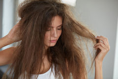 Kvinna med att rymma långt skadat torrt hår Hårskada, Haircare arkivfoton