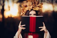 Kvinna med Autumn Leaves Crown Reading en bok Arkivbild