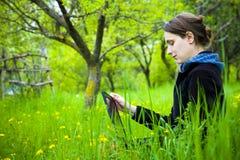 Kvinna med bärbar dator i fält Arkivbild