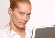 Kvinna med bärbar dator och hörluren Royaltyfria Bilder